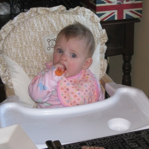Baby eating a carrot in a high chair
