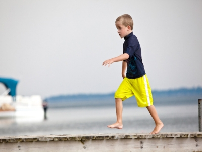 Young boy walking on a wharf