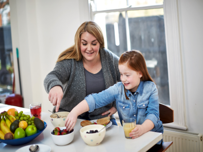 larger mother and daughter preparing food